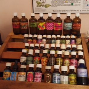 30-40 aromatherapy oils in bottles, stacked on wooden shelves
