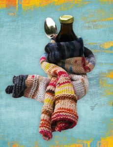 medicine and spoon wrapped in a comforting scarf to represent natural cold and flu treatments